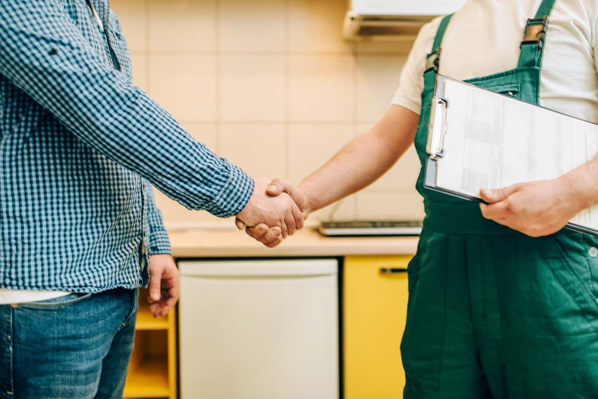 Domestic appliance installer and customer shaking hands