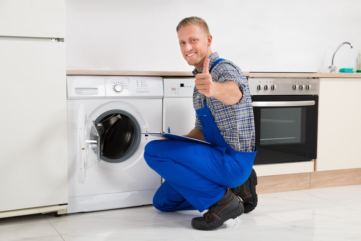 Domestic appliance installer looking at the camera with his thumb up after installing washing machine